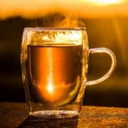 skodelica čaja v ozadju sončni zahod